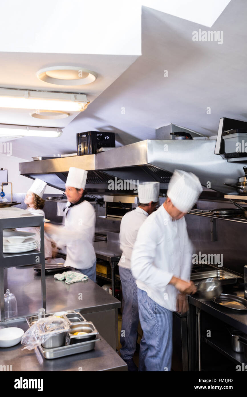 Team of chefs preparing food in the kitchen - Stock Image