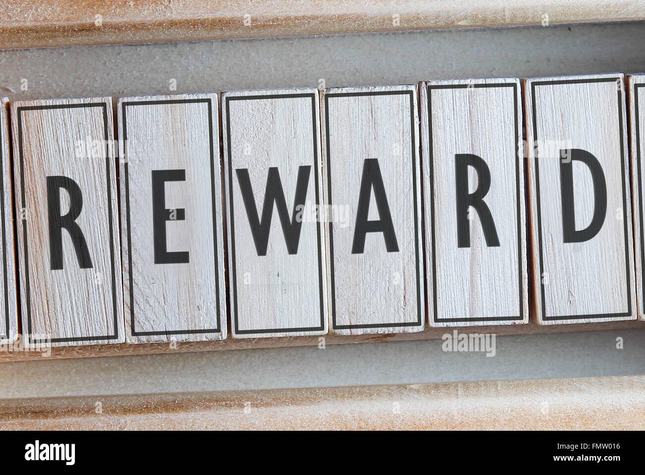 Reward word written on wood - Stock Image
