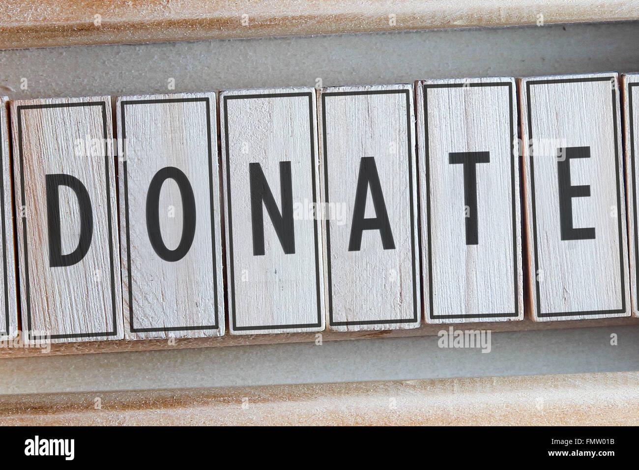 Donate word written on wood - Stock Image