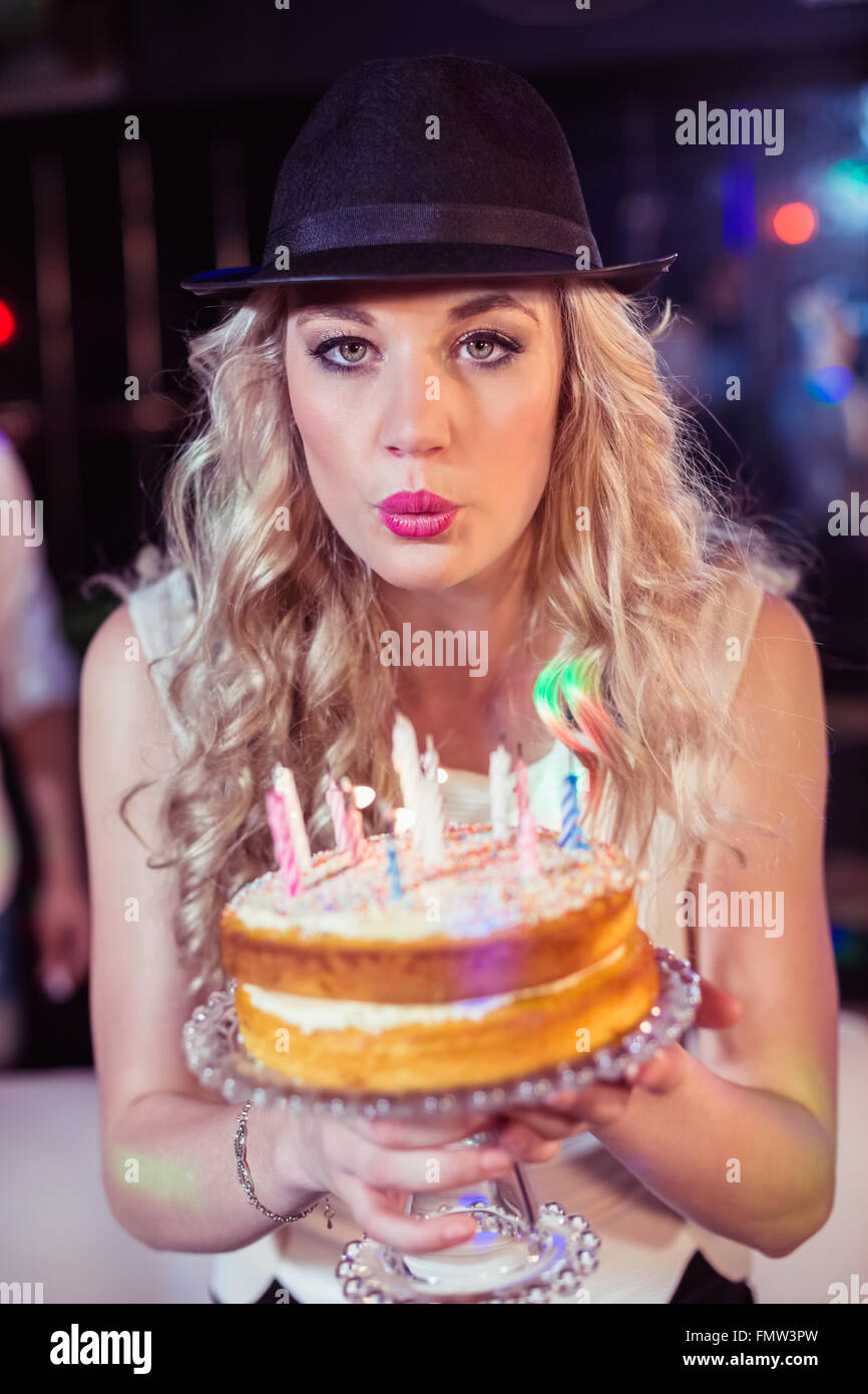 Woman blowing out candles - Stock Image