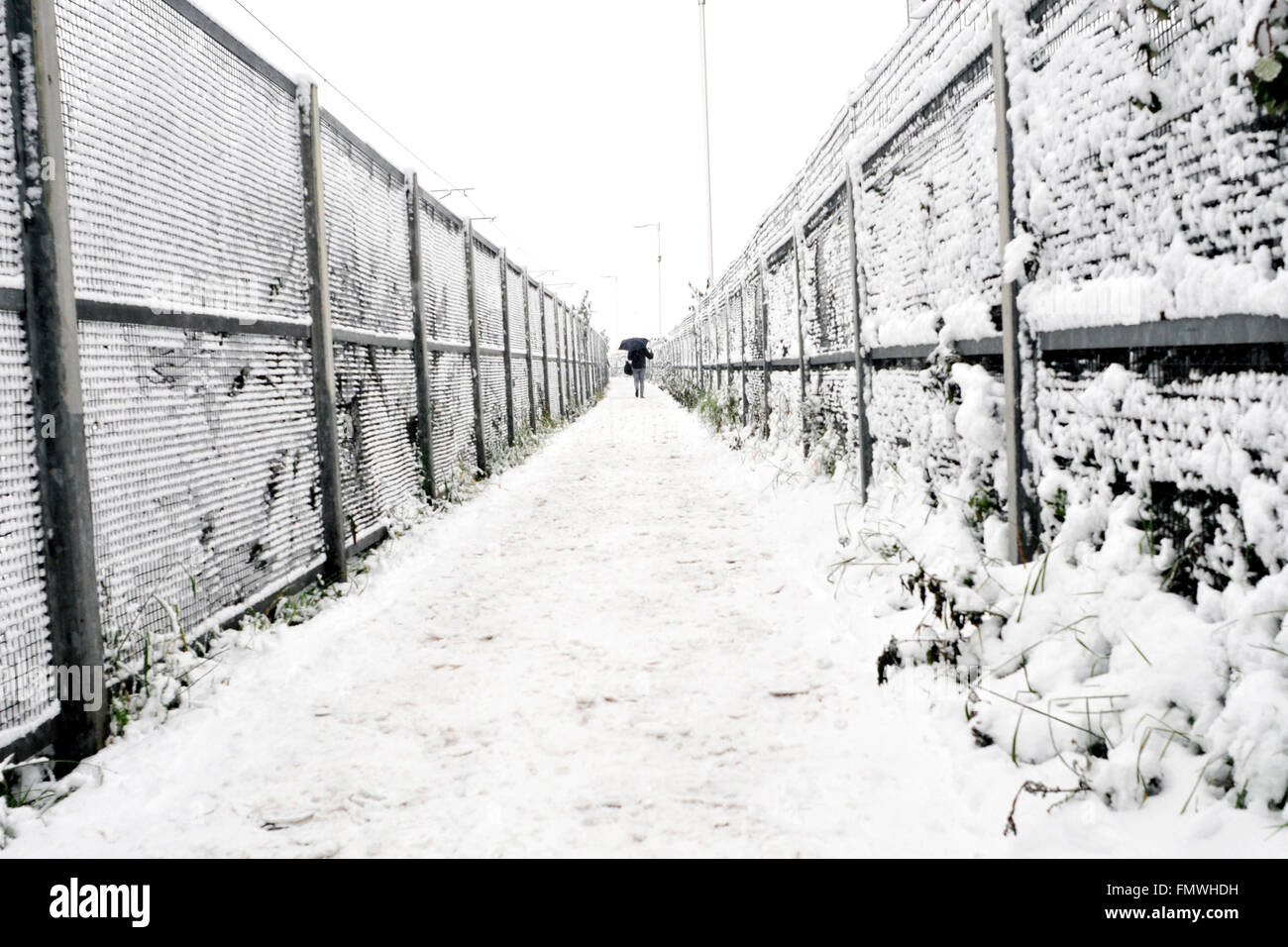 A man walks in a heavy snow towards Willesden Junction. - Stock Image