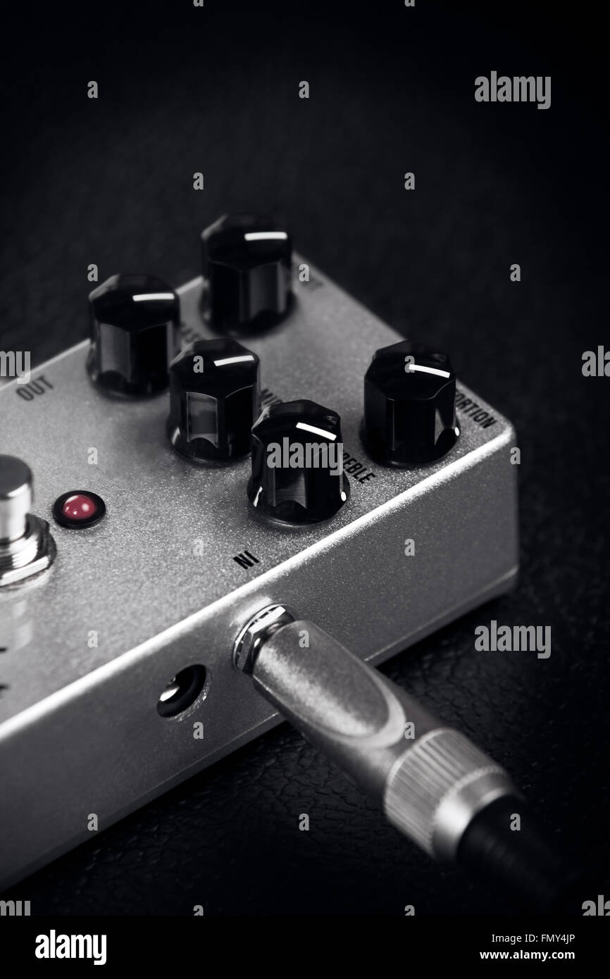 A guitar distortion pedal on a black background - Stock Image
