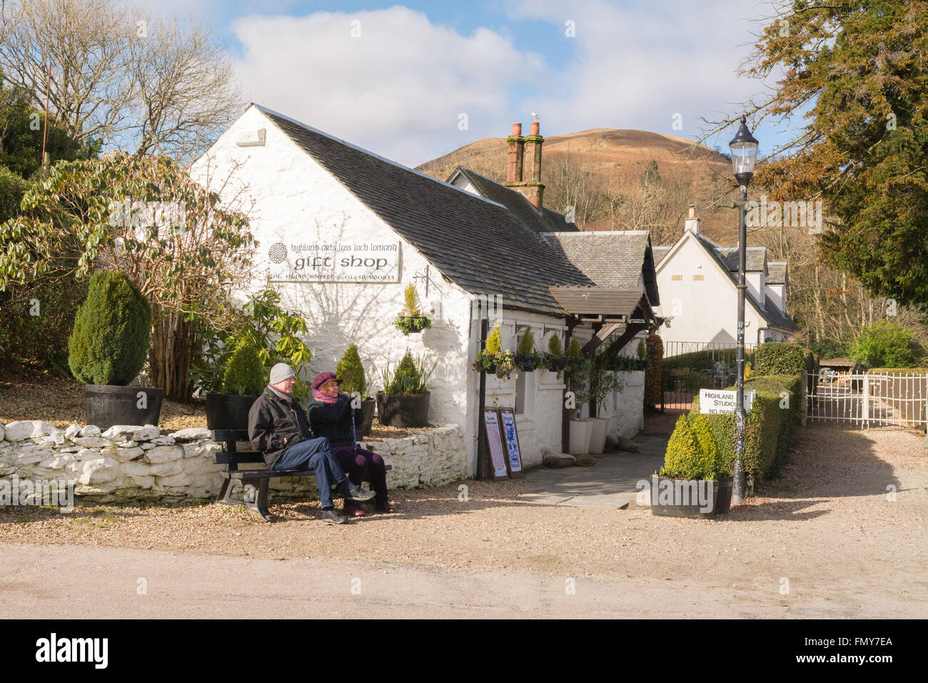 middle aged couple enjoying early spring sunshine outside the gift shop in Luss, Loch Lomond, Scotland, UK - Stock Image