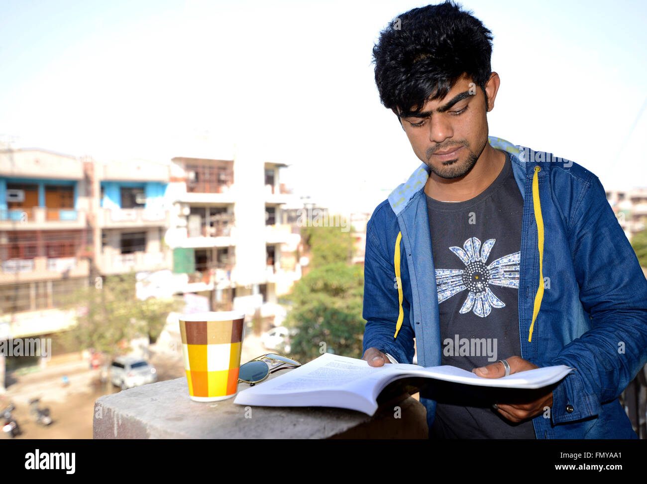 Handsome man reading on balcony - Stock Image