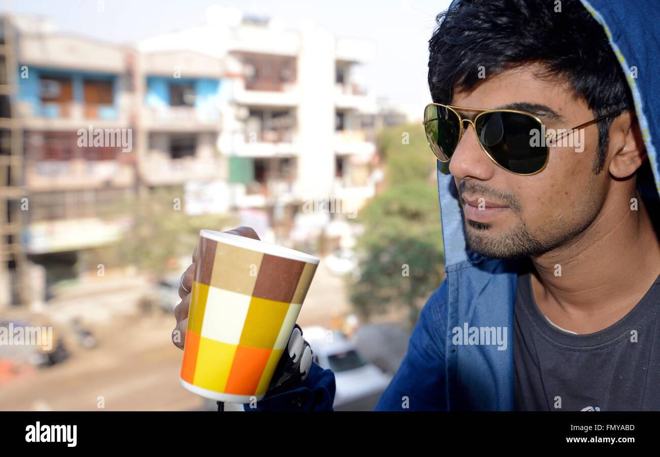 Handsome guy drinking tea on Balcony - Stock Image