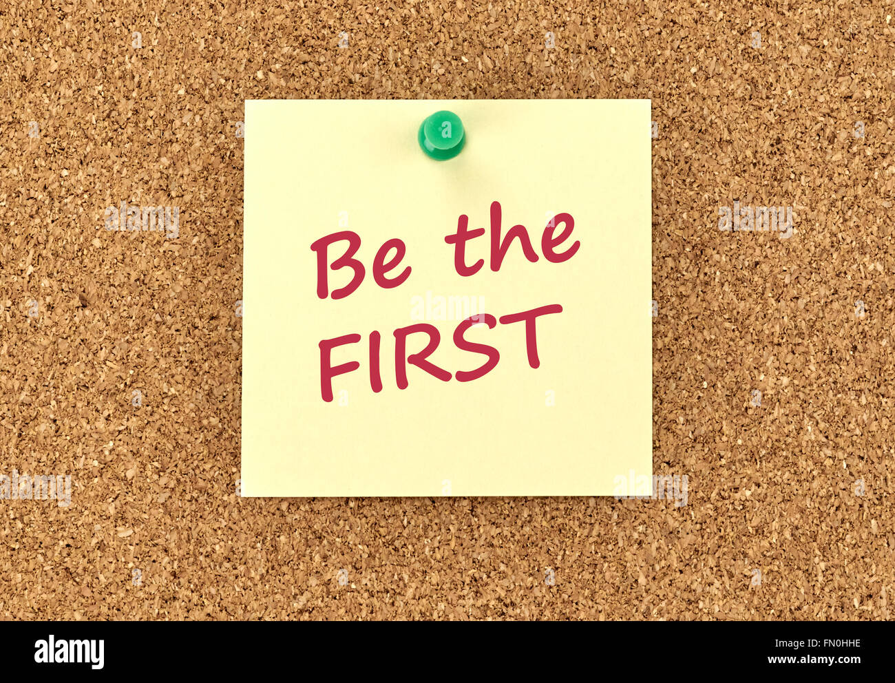 The phrase Be The First in red text on a yellow sticky note posted to a cork notice board. - Stock Image