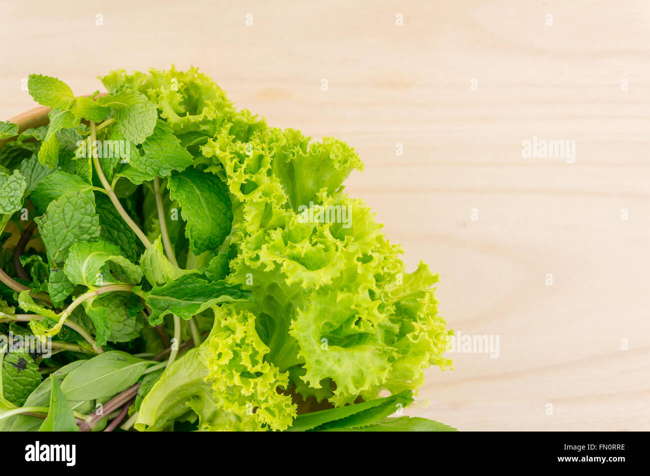 Green vegetables in wooden plate  on wooden background. Selective focus. - Stock Image