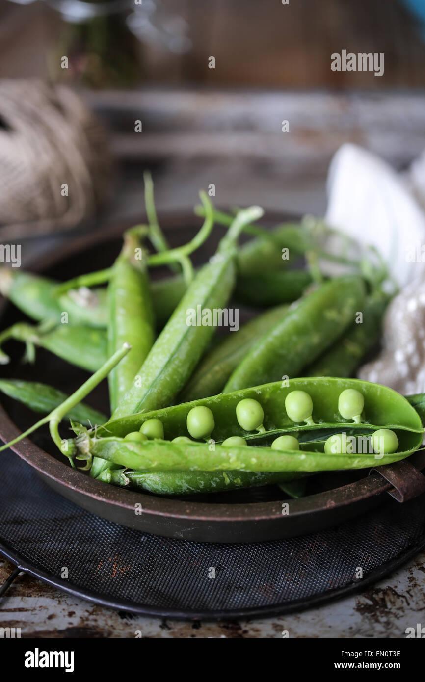 Fresh peas on a dark grey background - Stock Image