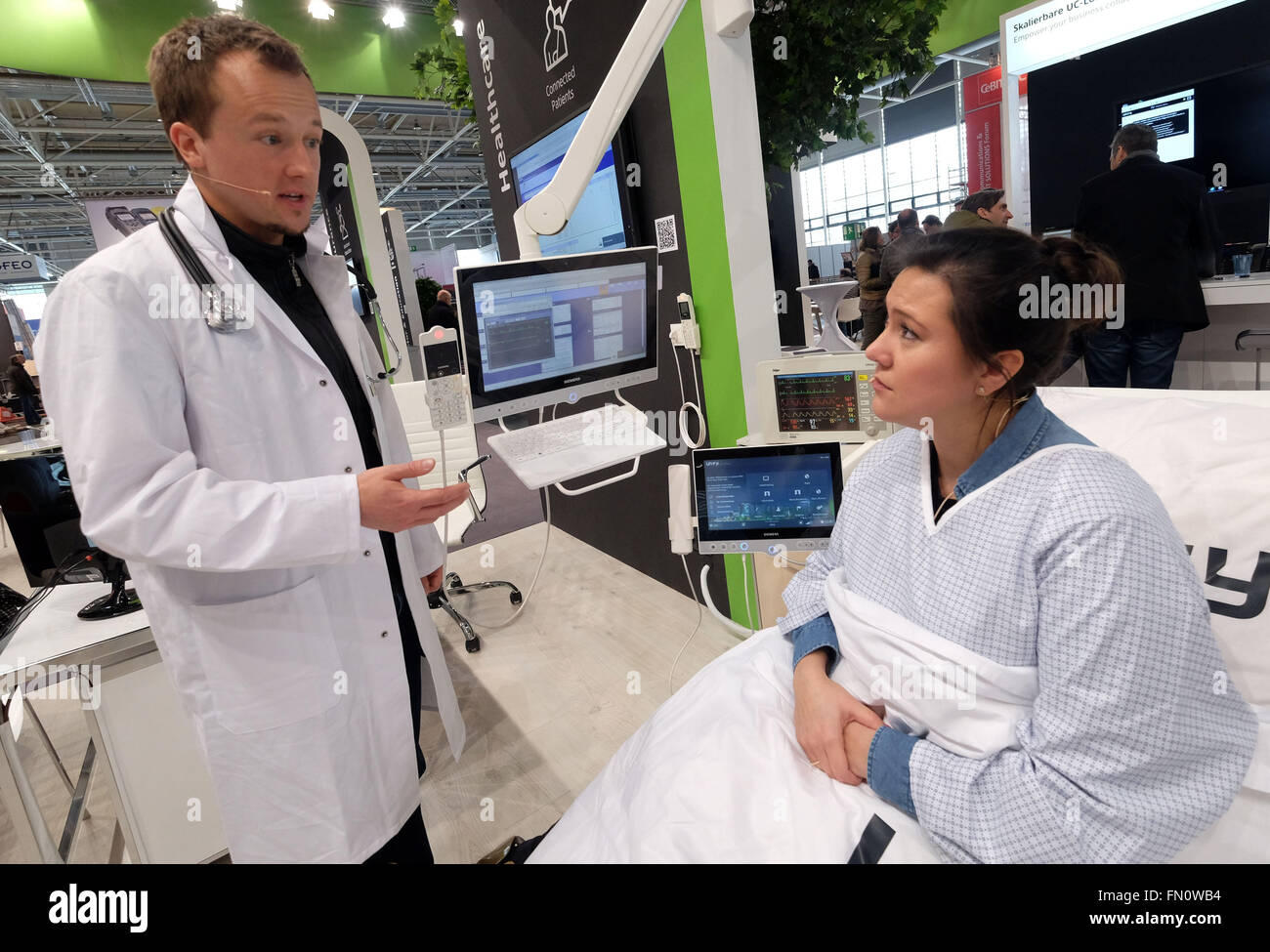 Hanover, Germany. 13th Mar, 2016. Two employees demonstrate the networked hospital bed of the future at the Unify - Stock Image