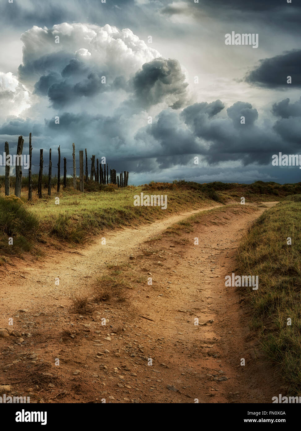 Road, fence line and thunderstorm near Coal Mine Canyon, Arizona - Stock Image