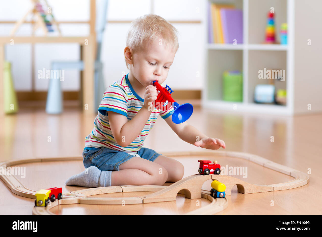 Child playing with wooden railway on the floor in nursery. Little boy plays a pipe imagining the train driver that - Stock Image