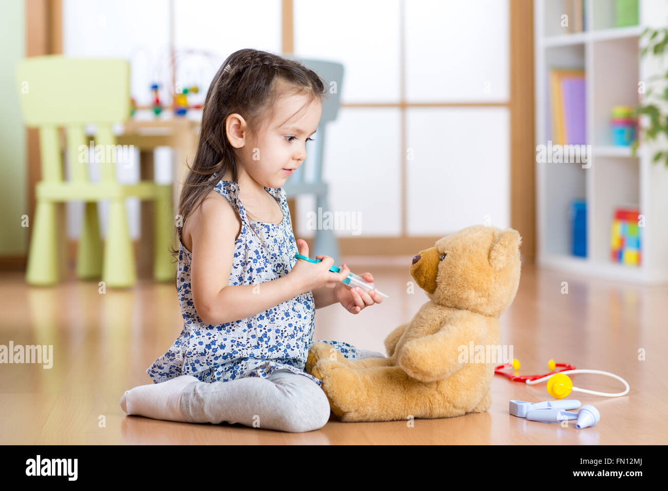 kid playing a doctor in children room - Stock Image