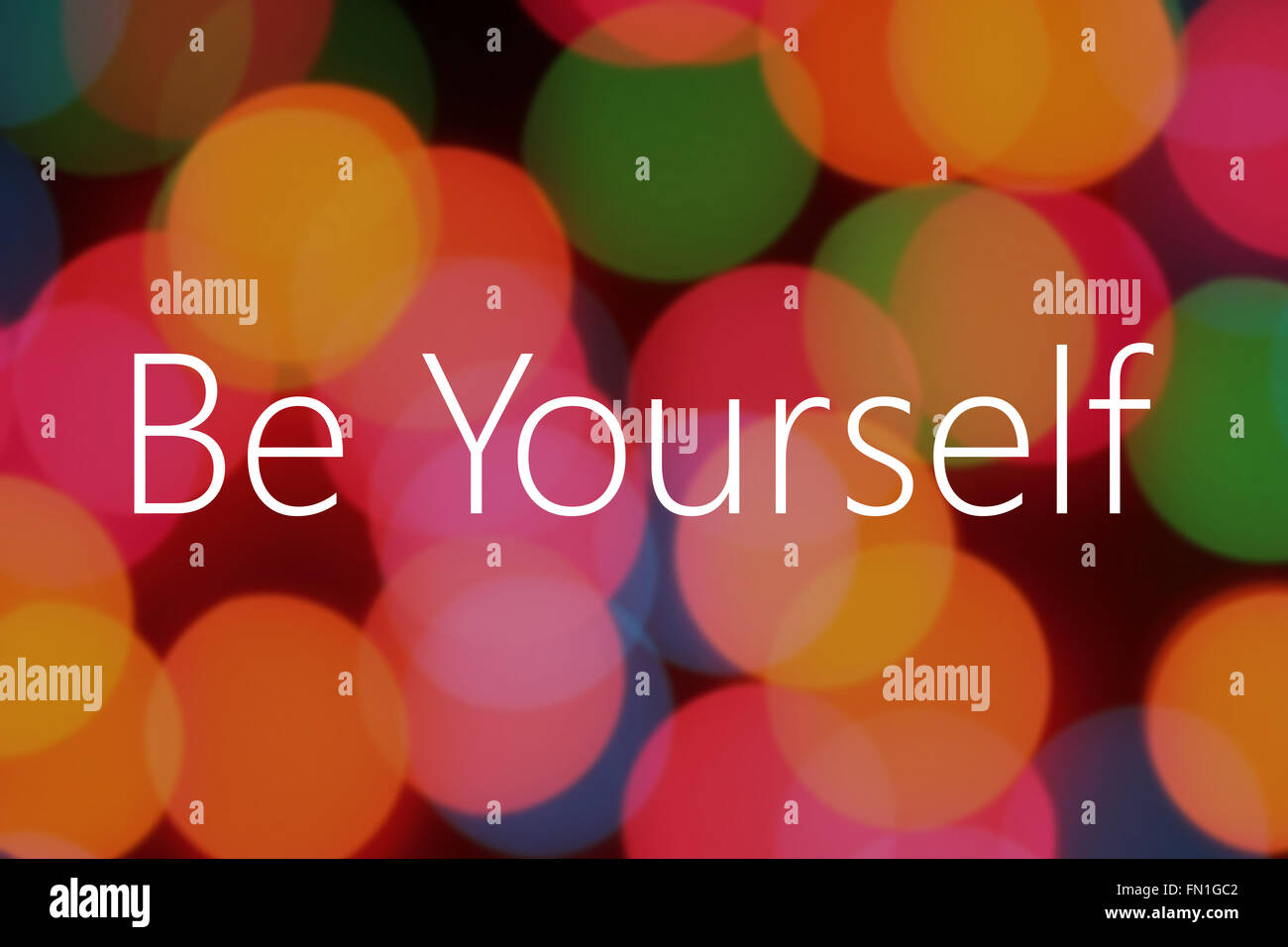Be yourself text on colorful bokeh background - Stock Image