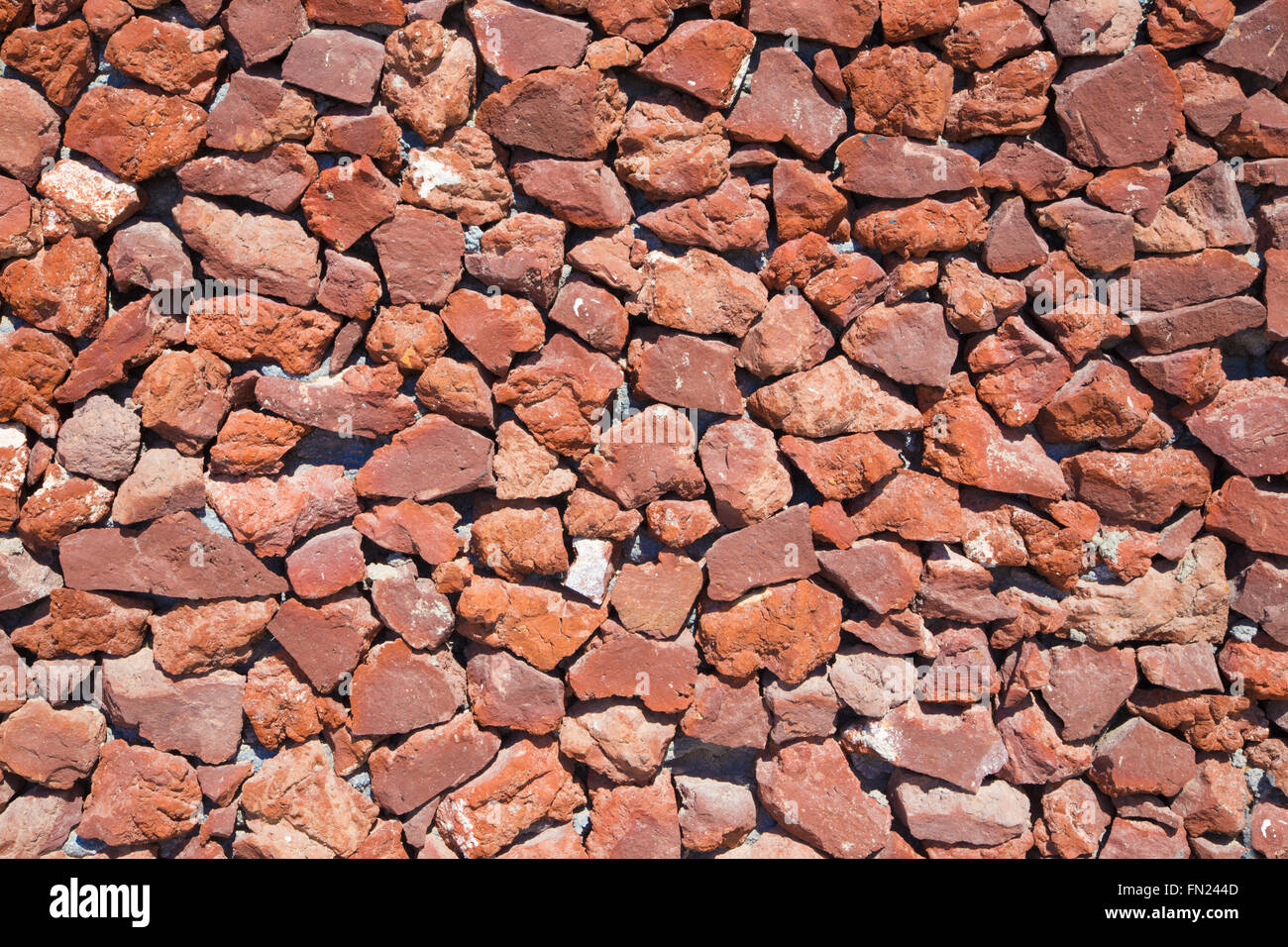 Santorini - Red pumice wall background - Stock Image