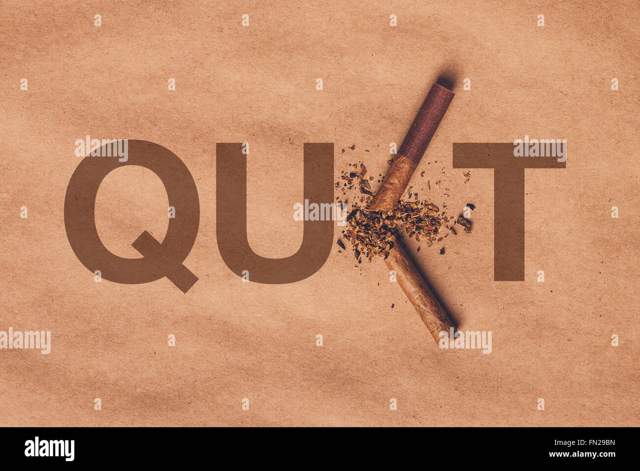 Broken cigarette top view over brown paper, quit smoking concept, warm retro image tone. - Stock Image