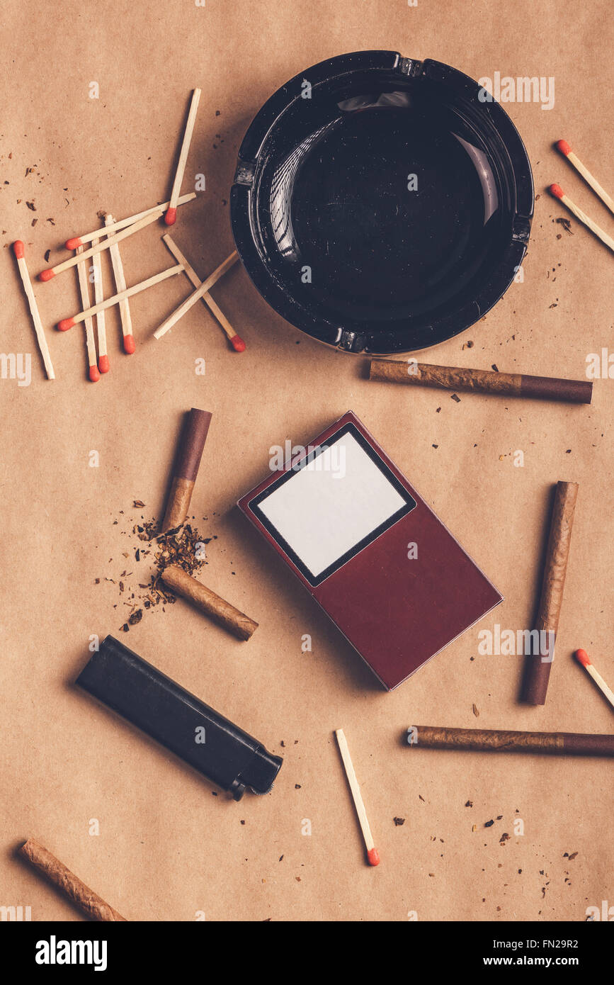 Passionate smoker flat lay table top view arrangement, warm retro toned image of ashtray, cigarettes, matches and - Stock Image