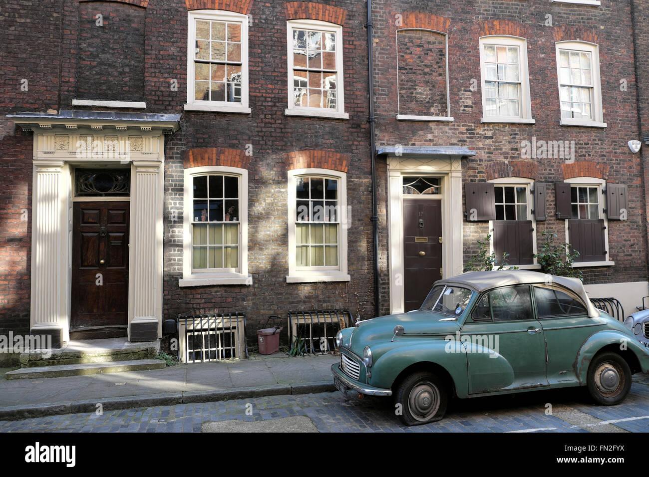Morris Minor car with a flat tire parked on Elder Street in Spitalfields, London E1  KATHY DEWITT Stock Photo