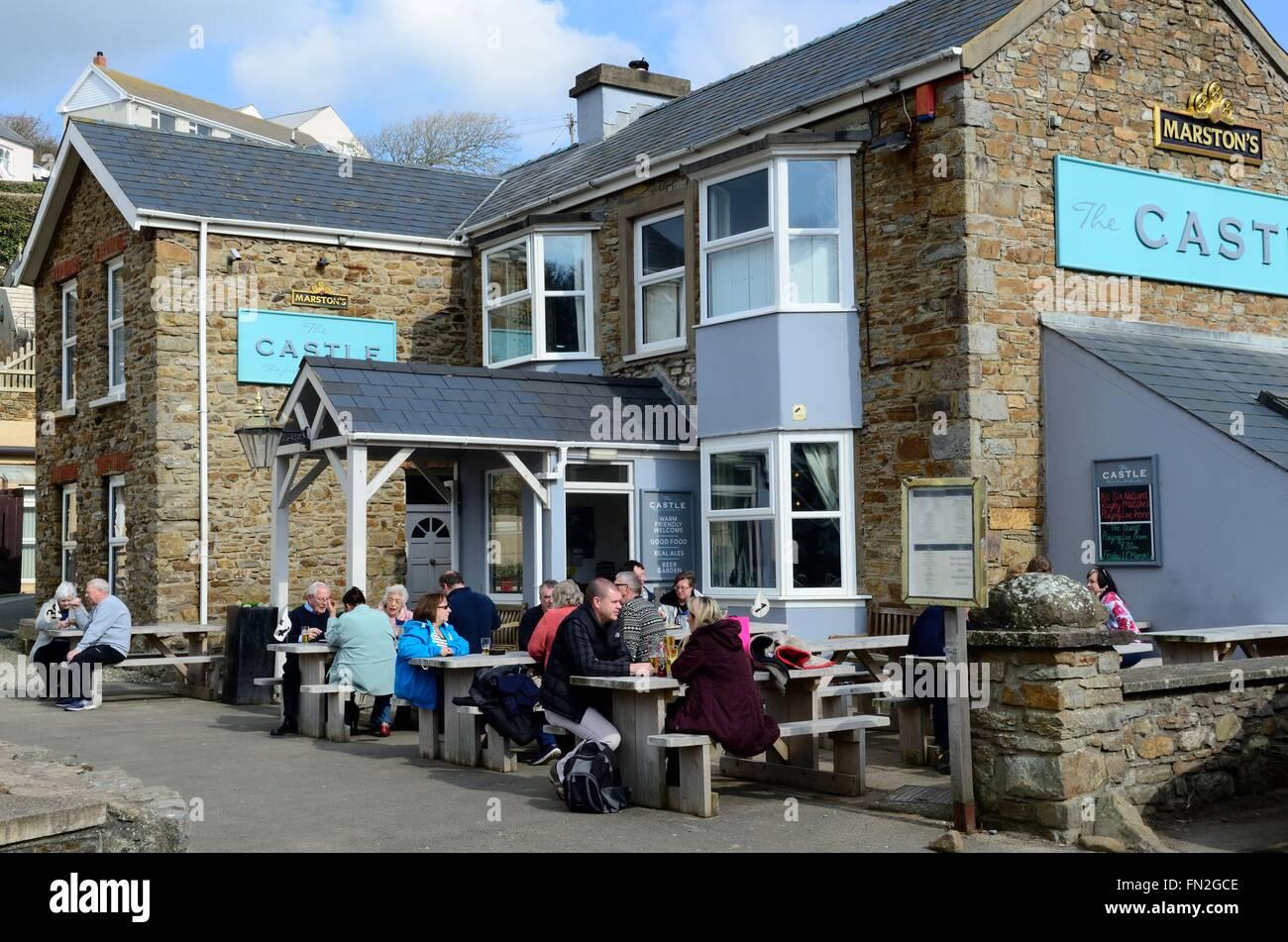 people enjoying the spring sunshine outside The Castle Little Haven Pembrokeshire Wales Cymru UK GB - Stock Image