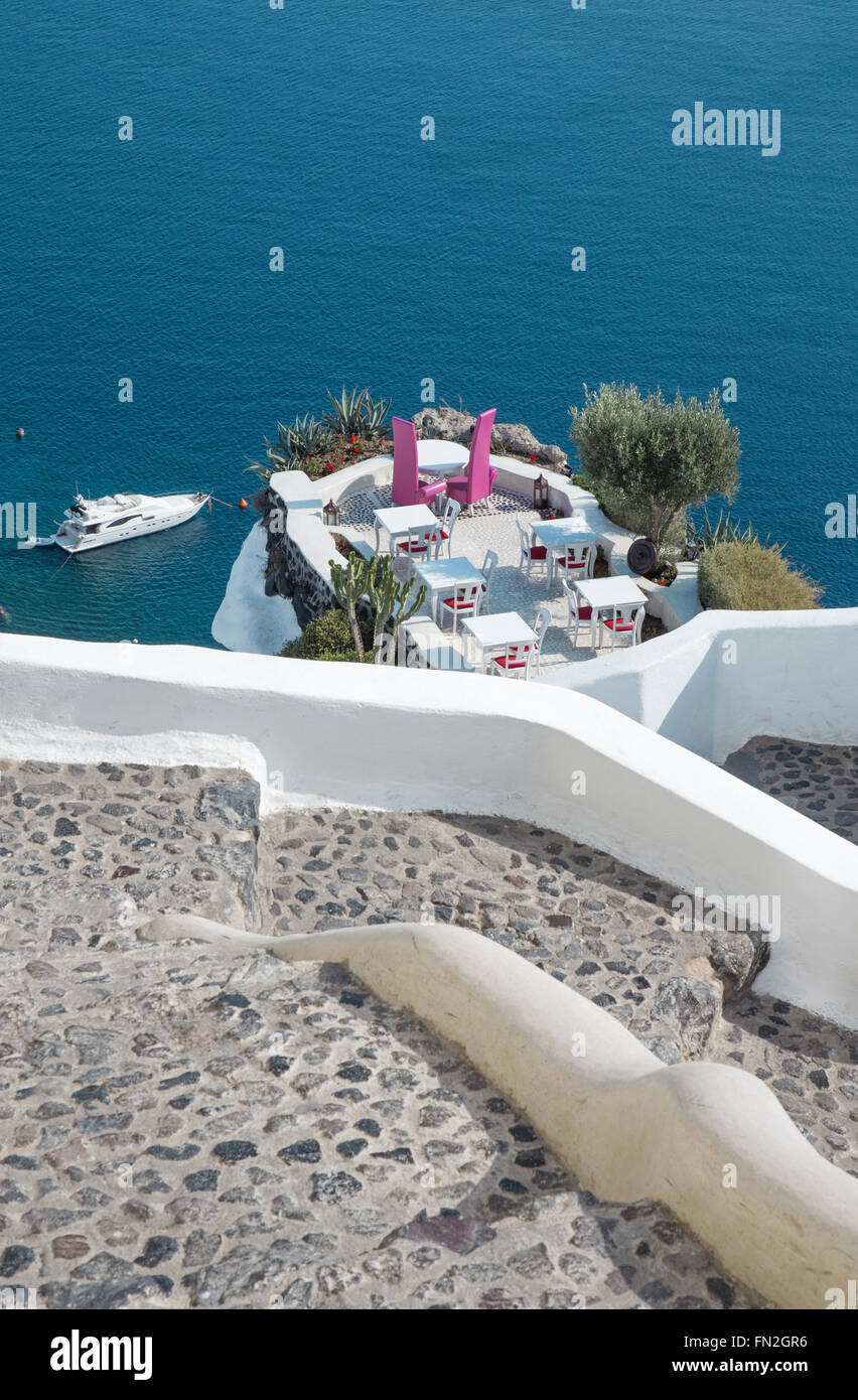 Santorini - The restaurant geared to wedding romantic dinner in Oia (Ia) and the yacht under cliffs in the background. - Stock Image