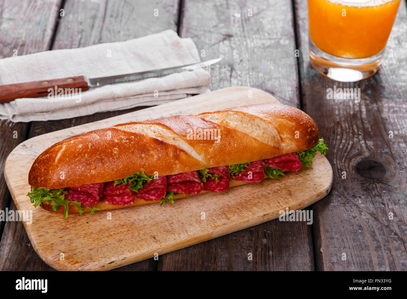 baguette sandwich with salami and herbs on a wooden surface Stock Photo
