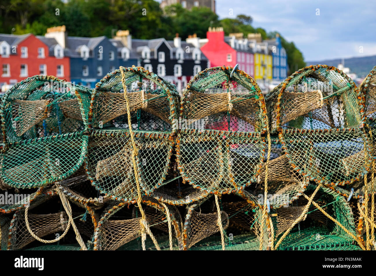 Lobster pots and picturesque painted houses in the port of Tobermory, on the Isle of Mull, Inner Hebrides, Scotland - Stock Image