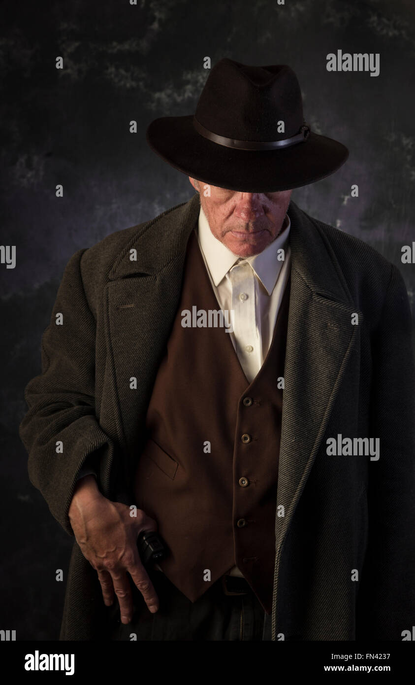 Sinister looking man wearing overcoat and hat with one hand over belted pistol against portrait background in low - Stock Image