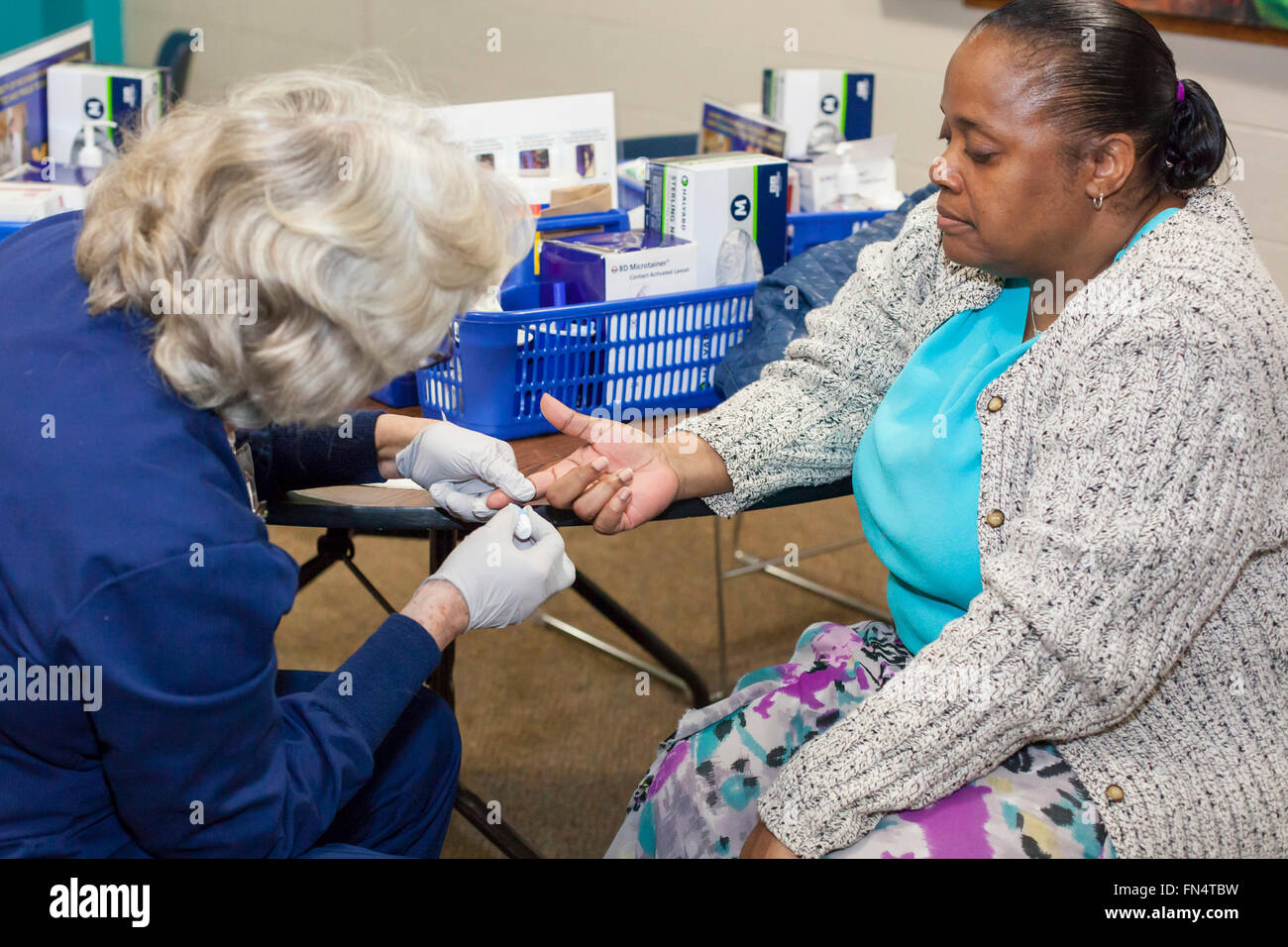 Flint, Michigan - Darron Garrett (right) has her blood drawn by volunteer nurse Bonnie Hudson to test for lead exposure. - Stock Image