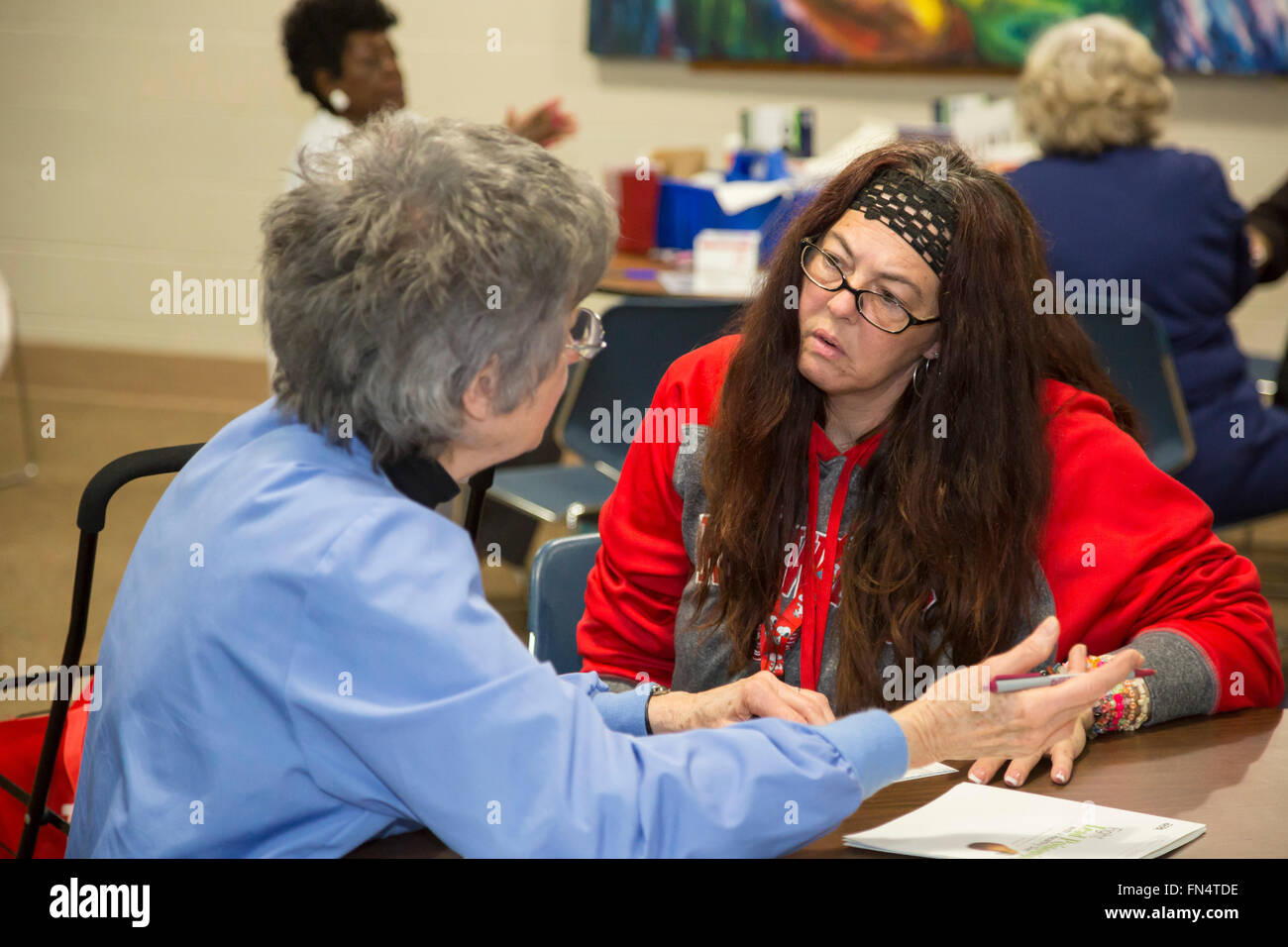 Flint, Michigan - Janet Barnfather (left) explains the results of a blood test for lead exposure to Michele Fiebecker. - Stock Image