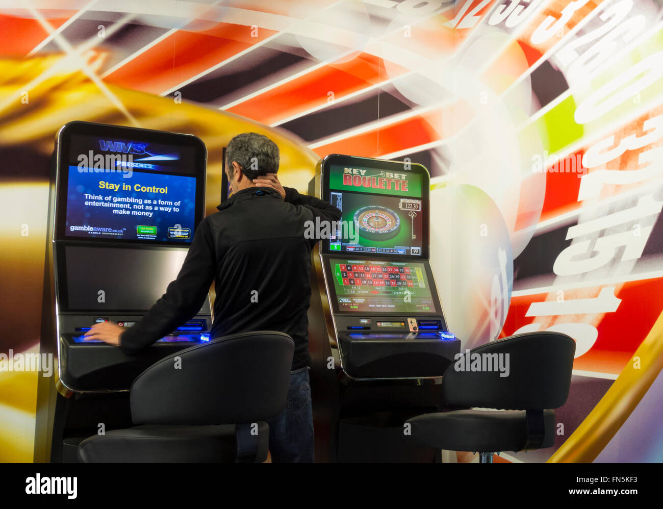 Mature man using fixed odds betting terminal showing stay in control message on screen in Bookmakers. England, UK Stock Photo