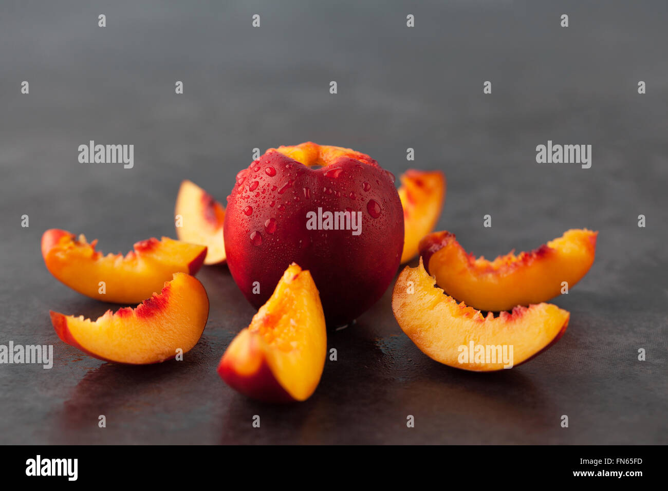 Yellow nectarine peach - whole fruit and slices on dark grungy  background. Shallow depth of field. - Stock Image