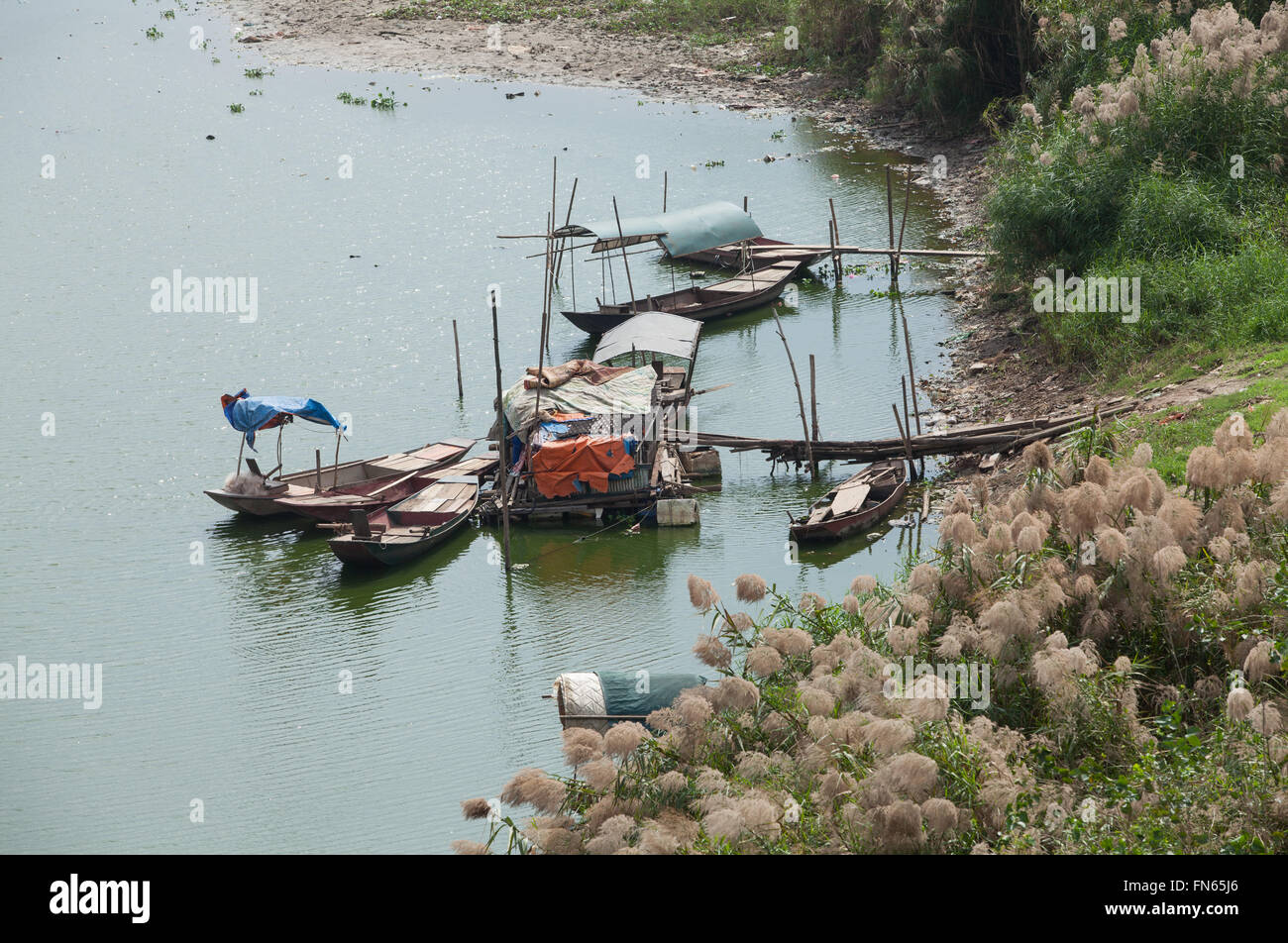 Poor floating village, slumdog are on the bank of Red river, only 2km from the center of Hanoi capital. - Stock Image