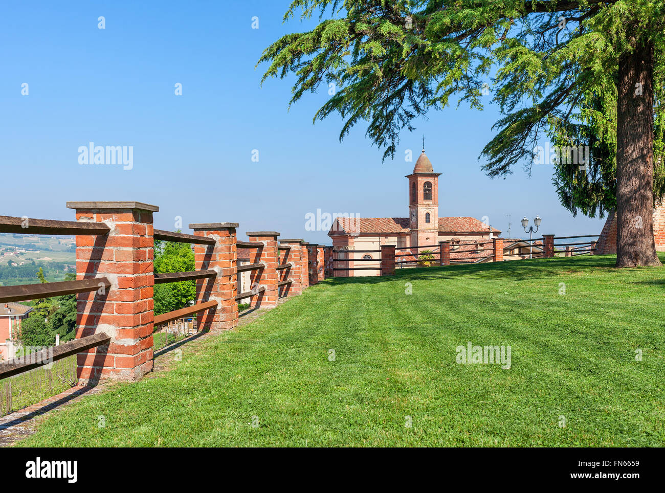 Brick fence along green lawn as small parish church on background under blue sky in Piedmont, Northern Italy. - Stock Image