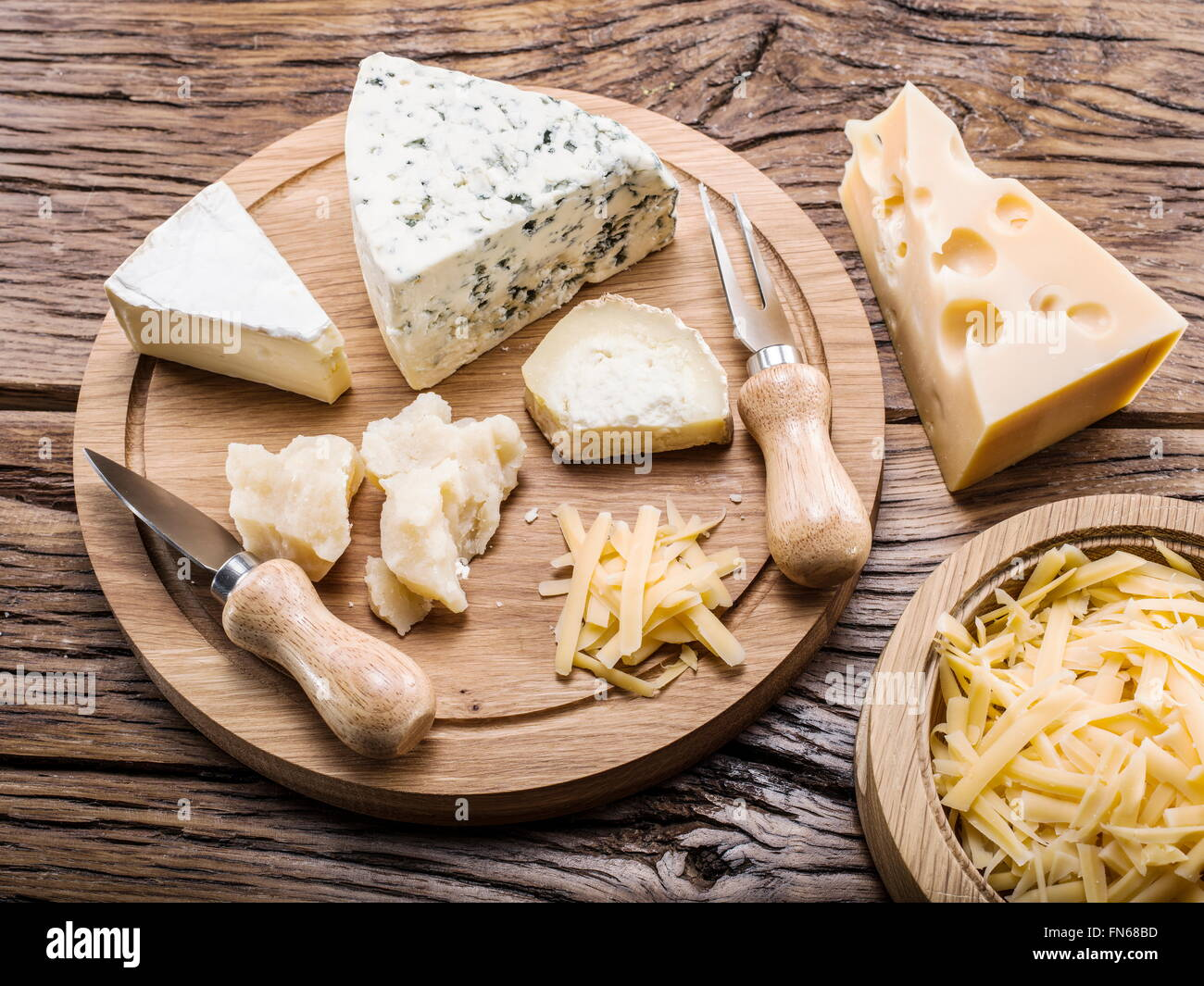 Variety of cheeses on a wooden board. - Stock Image