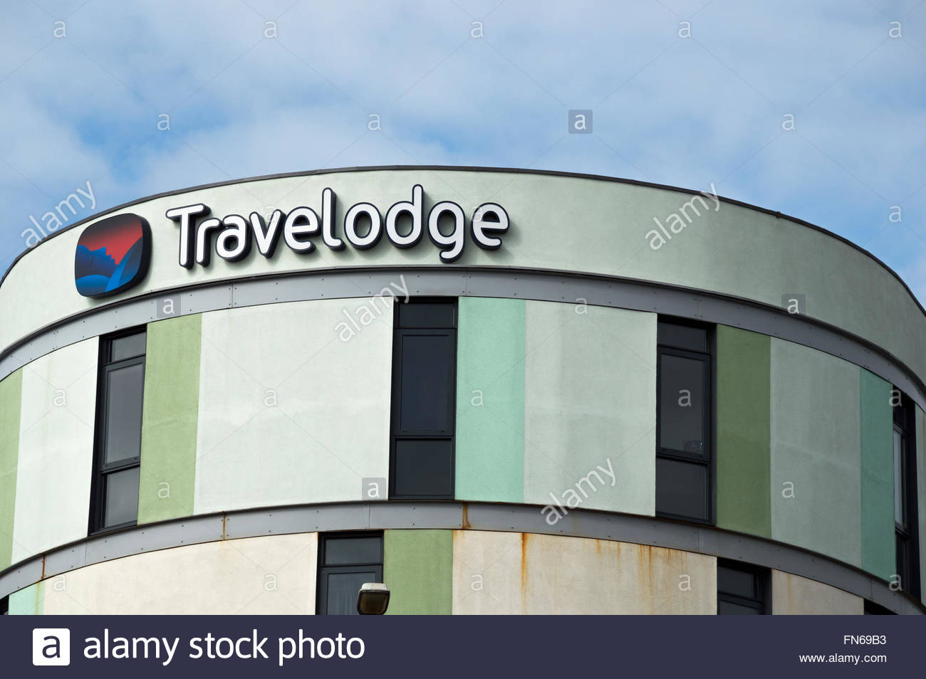 Looking up at the sign of the Maidstone Travelodge building with its many windows and multi-coloured exterior. - Stock Image