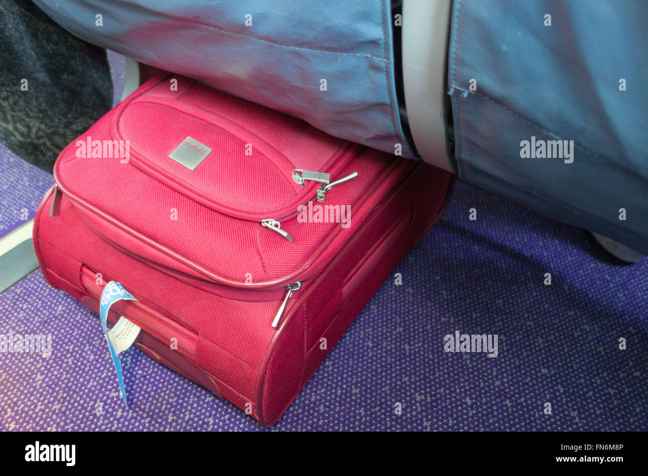Hand luggage stored underneath seat on flybe flight - Stock Image
