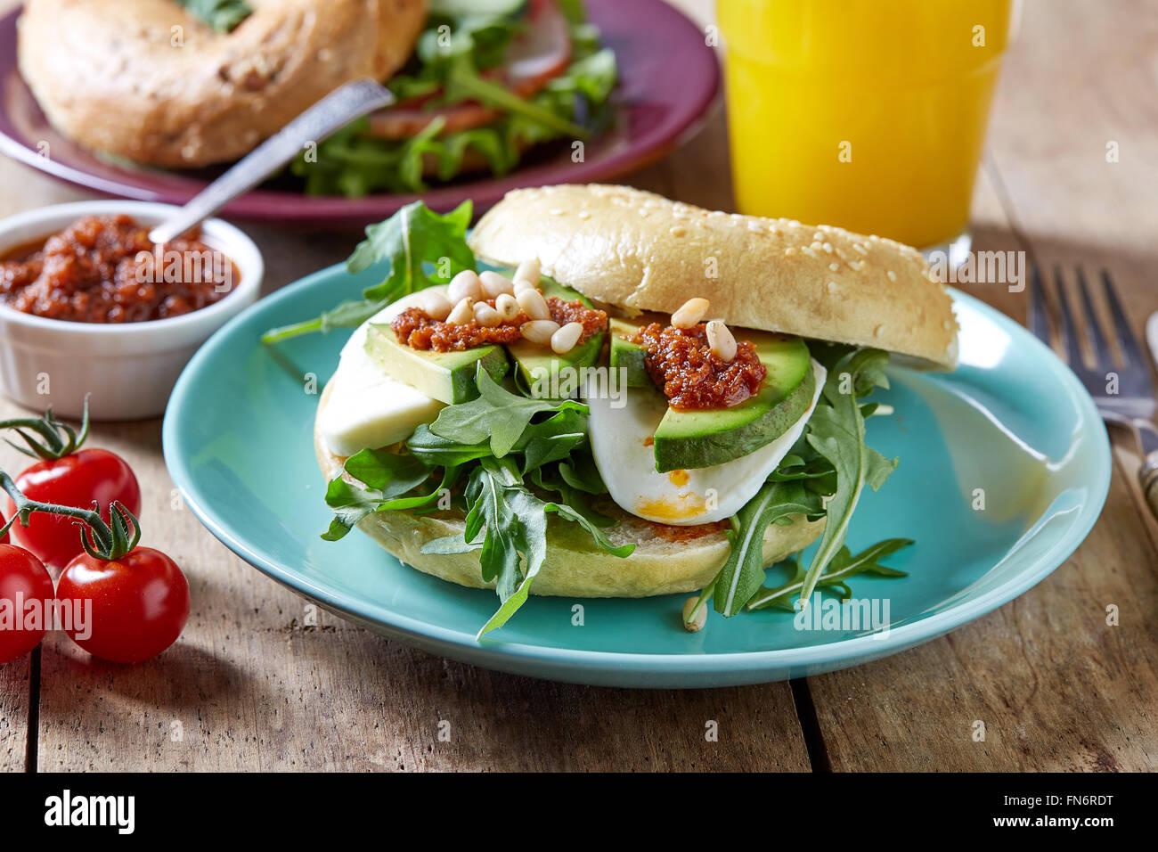 Fresh bagel sandwich on wooden table - Stock Image
