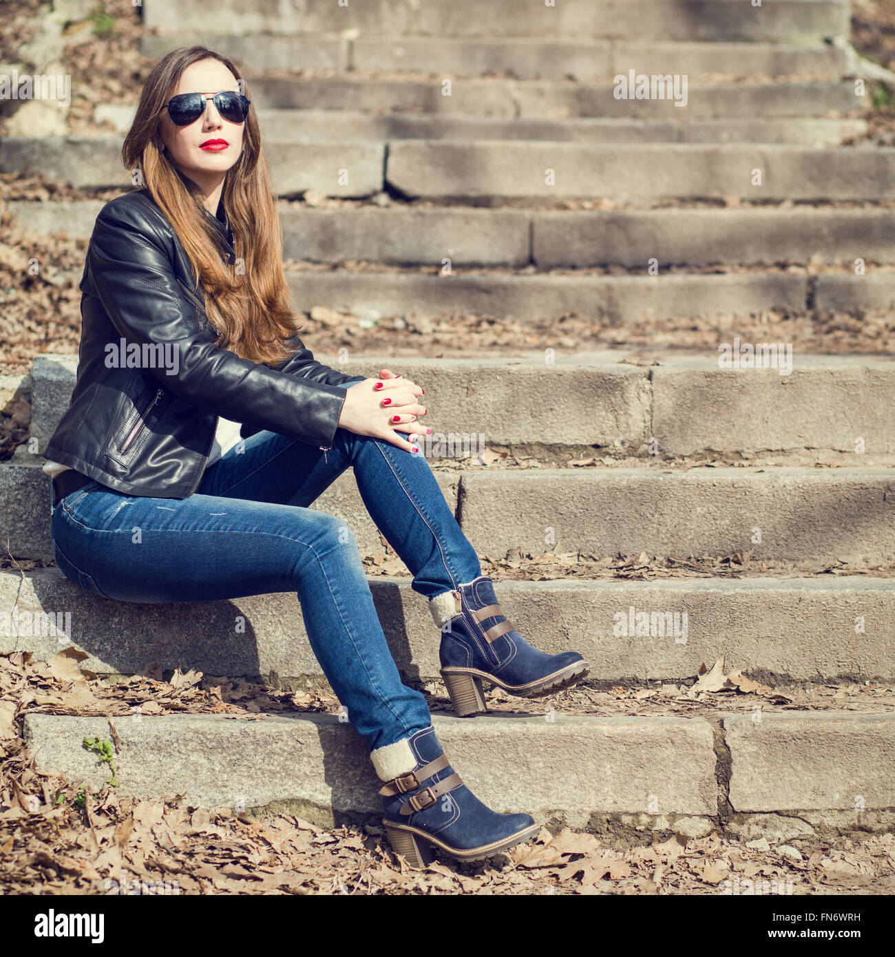 Young Stylish Woman In Jeans And Leather Jacket Resting On