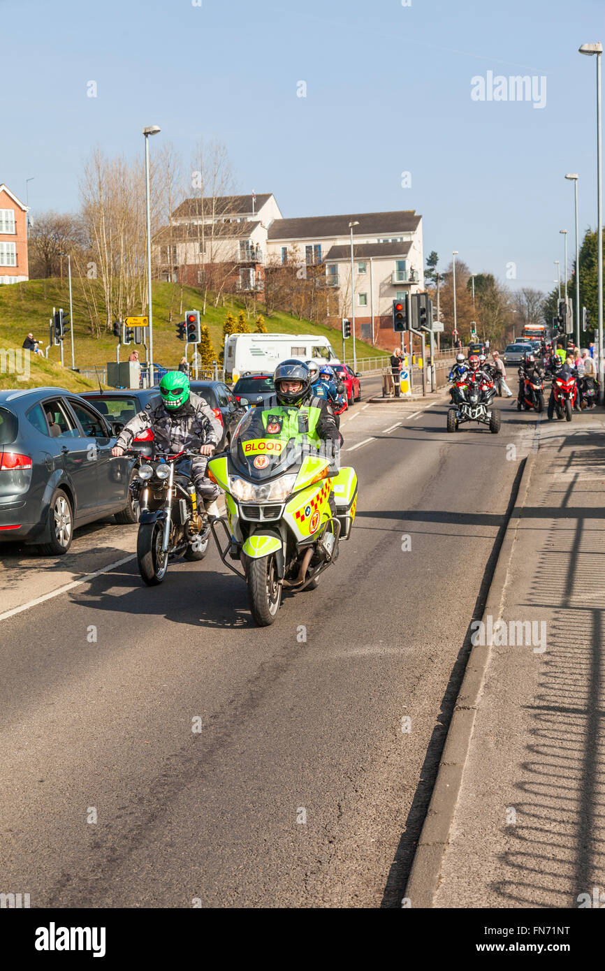 Stoke On Trent, Staffordshire, UK. 13th March, 2016. Blood Bike rider and man wearing a green skeleton safety helmet - Stock Image