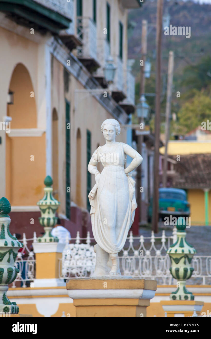statue of woman in front of buildings with classic car in the background at Trinidad, Cuba, West Indies, Caribbean - Stock Image