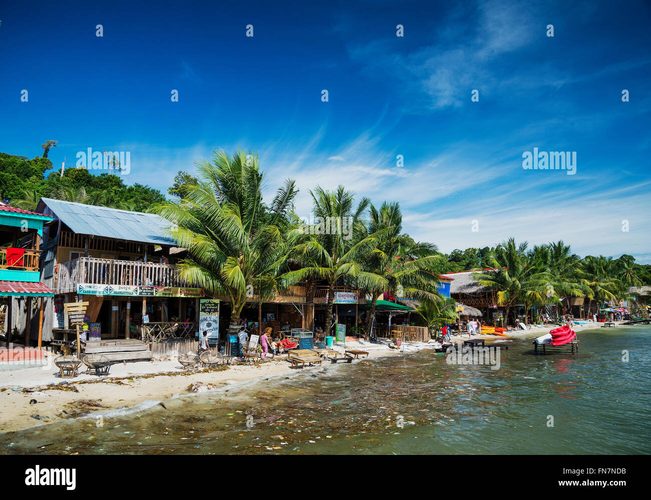 polluted dirty beach with garbage rubbish floating in sea on koh rong island cambodia Stock Photo
