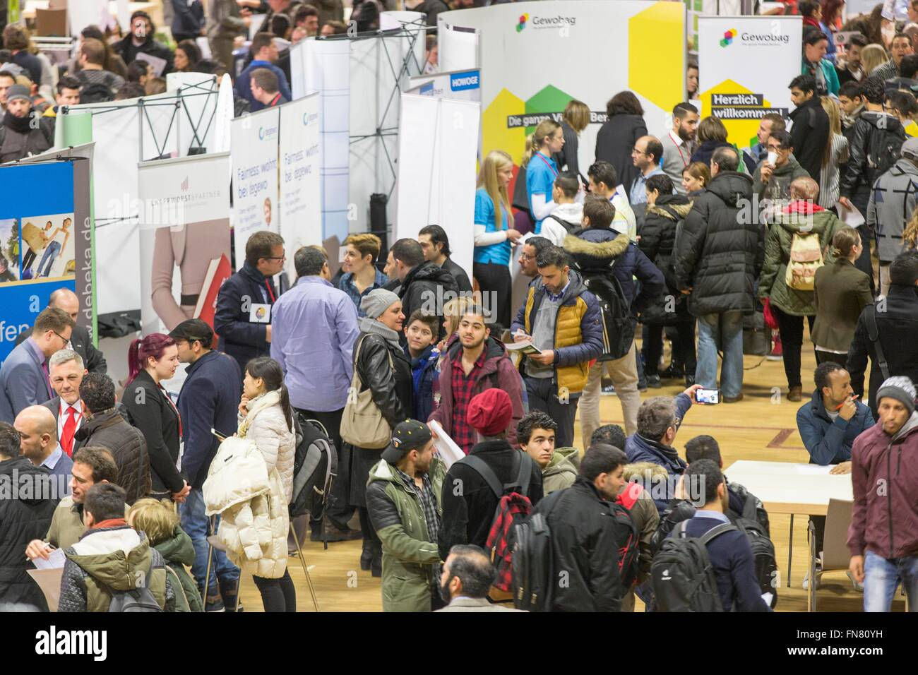Migrants and refugees walk around stands offering jobs and education at a job fair for refugees in Berlin, 29 February Stock Photo