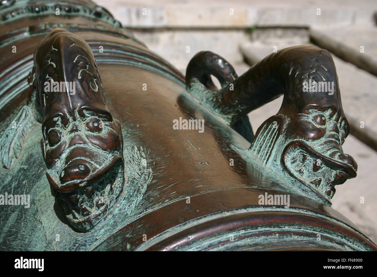 Snake or dragon handles on a bronze cannon with green patina in Malta. - Stock Image
