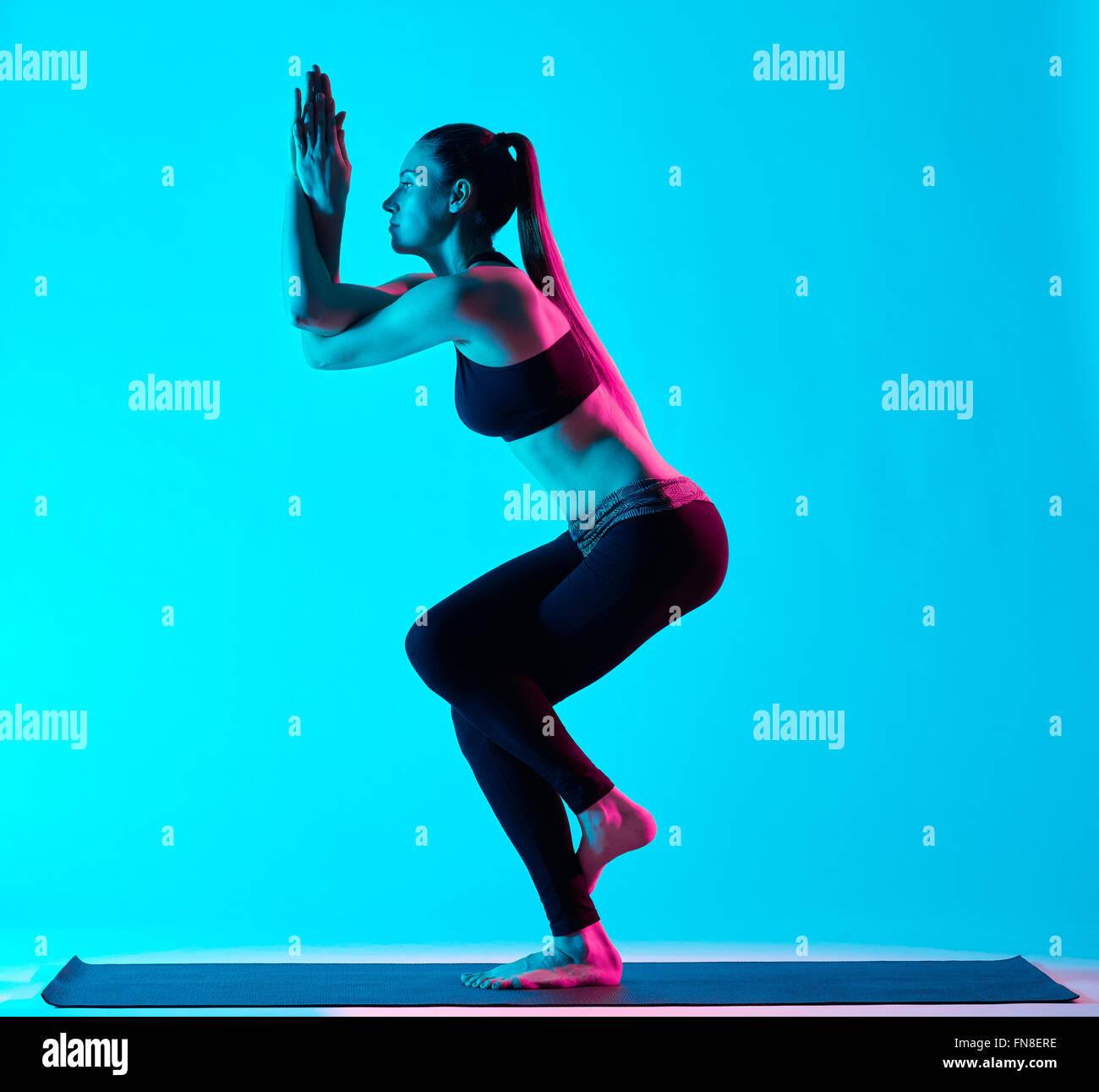 one caucasian woman exercising Garudasana eagle pose yoga exercices  in silhouette studio isolated on blue background - Stock Image