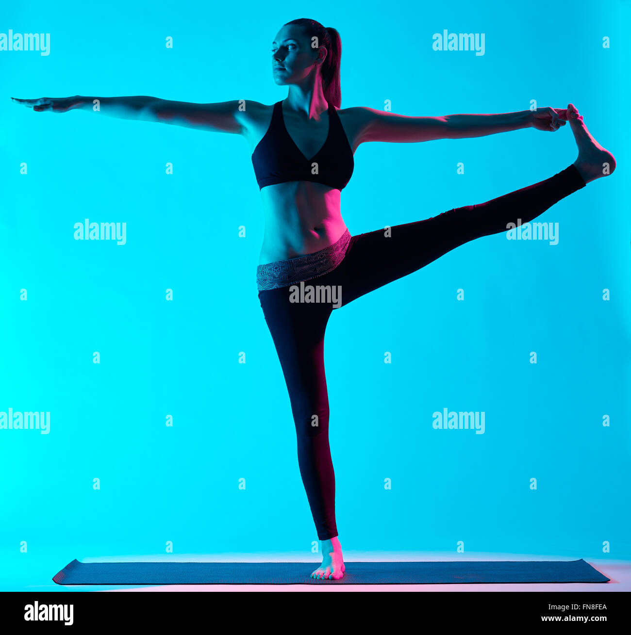 one caucasian woman exercising Hasta Padangusthasana yoga exercices  in silhouette studio isolated on blue background - Stock Image