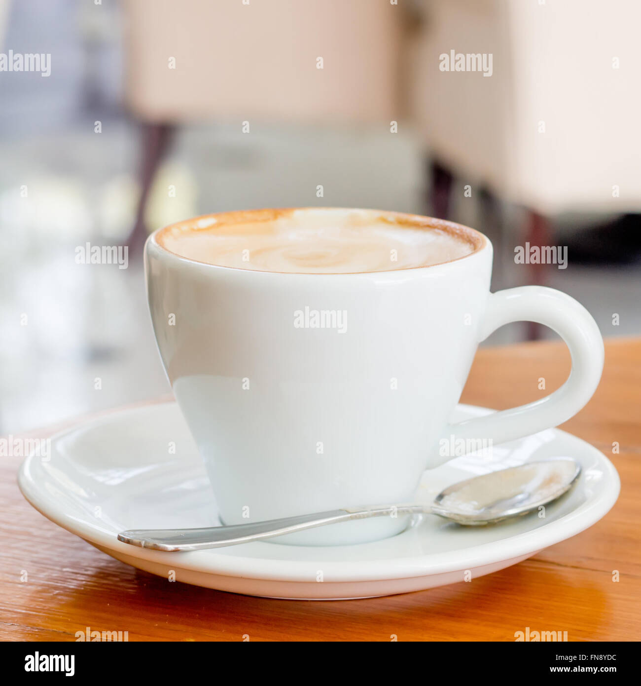 Cup of Art Latte coffee on the wooden desk Stock Photo