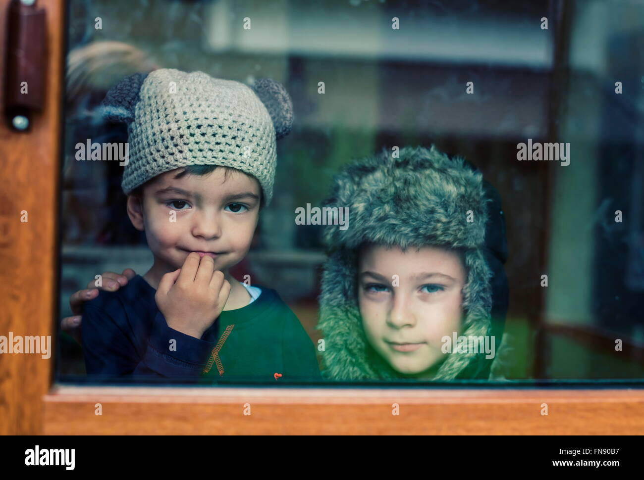 Two boys looking out of a window - Stock Image