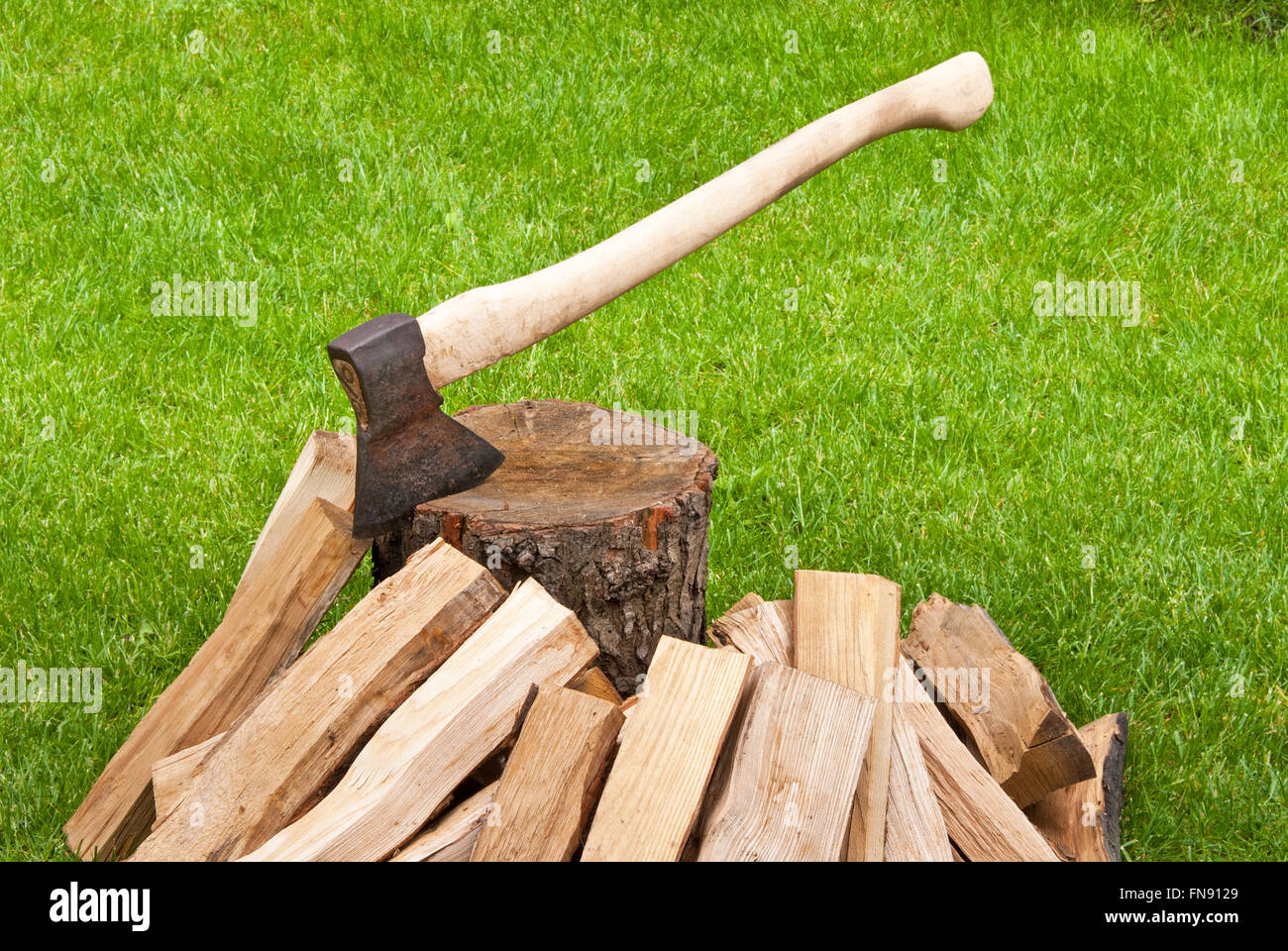 old used ax with a log in the garden Stock Photo
