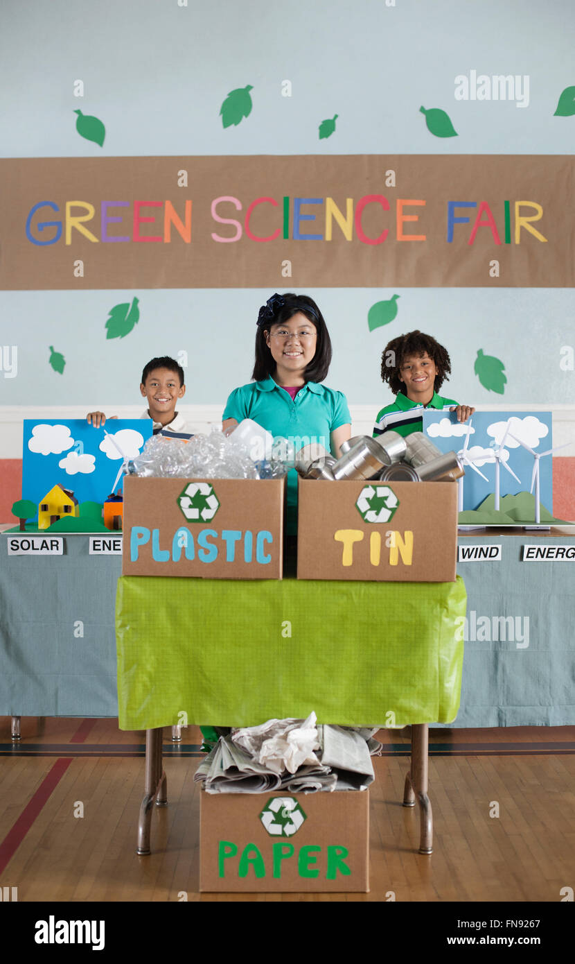three children standing behind presentations at the green science