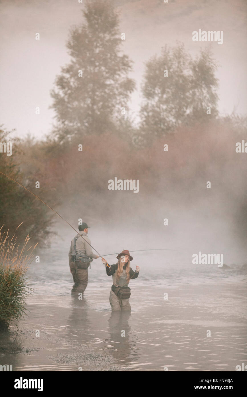A couple, a man and woman standing in mid stream fly fishing in a river. Stock Photo