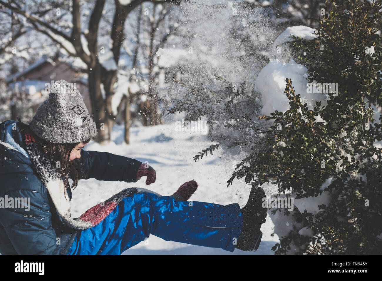 Girl kicking snow off a tree - Stock Image